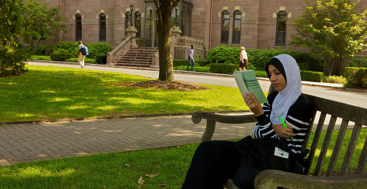 A Seton Hall Student Sitting on a Bench on Campus Reading