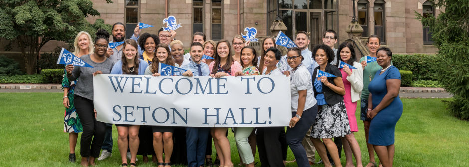 A photo of the admissions counselors team holding a Welcome to Seton Hall sign on the University Green.
