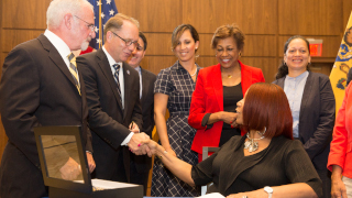 Acting New Jersey Governor Sheila Oliver shaking hands with incoming President Nyre. They are surrounded by other government members.